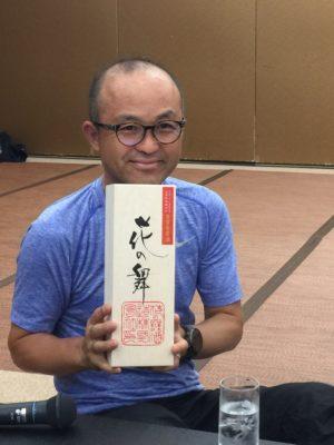 日本酒を手に嬉しそうな金哲彦さん